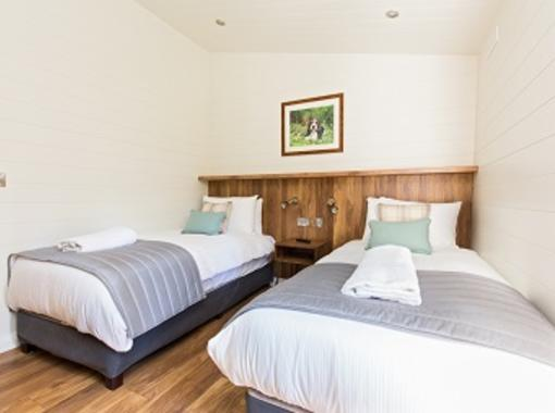 Twin beds with crisp white bedding and grey foot runner, feature wooden bed head
