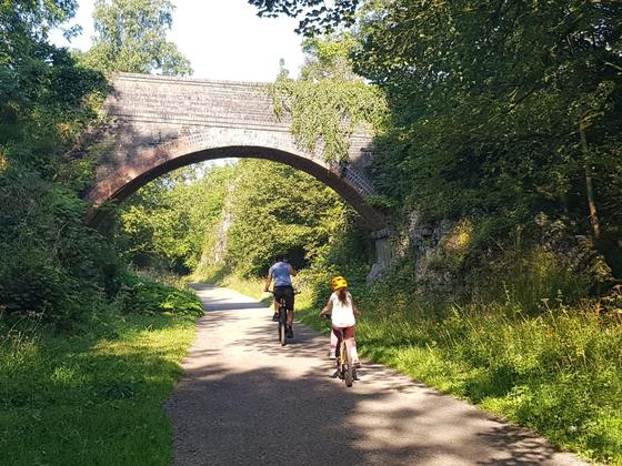 Adult and child cycling along the monsal trail