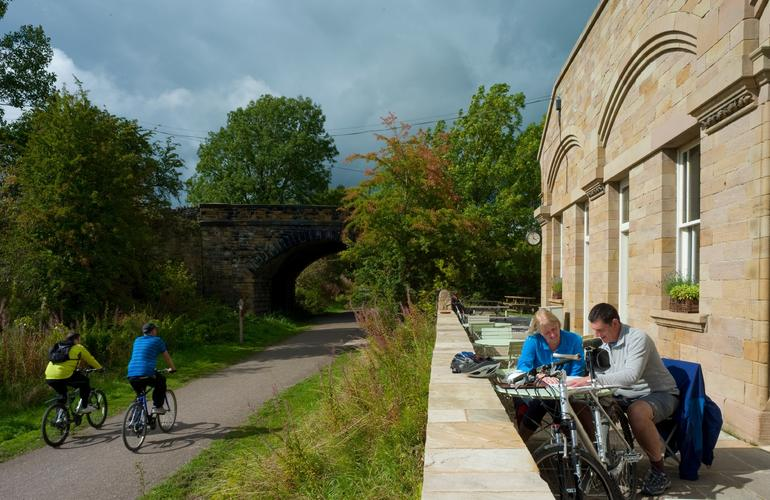 People cycling along the monsal trail at the side of the Hassop station cafe with people sat outside enjoying a bite to eat