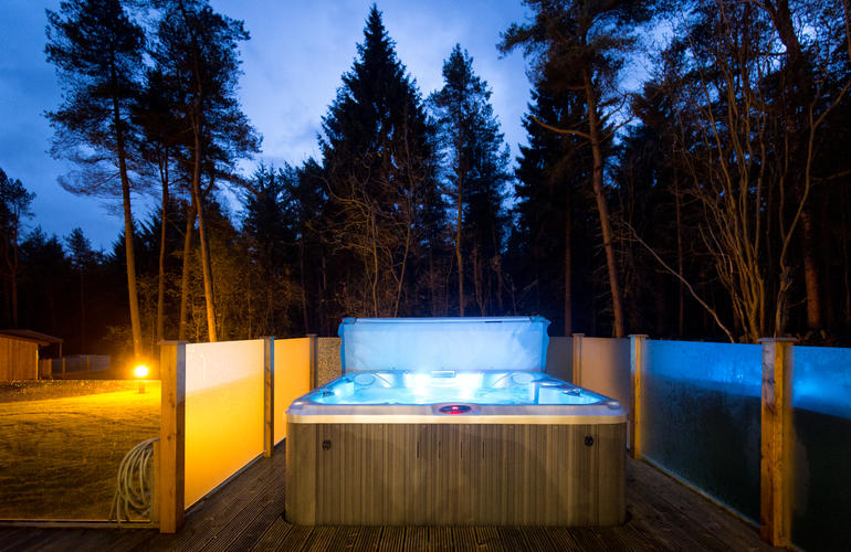Hot tub at nigh twith lights glowing in the hot tub and surrounded  by trees