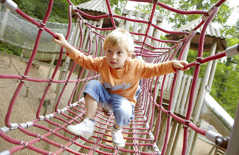 Child walking through rope tunnel