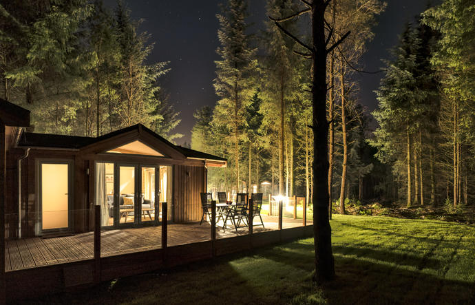 Lodge lit up at night in forest with stars in the sky