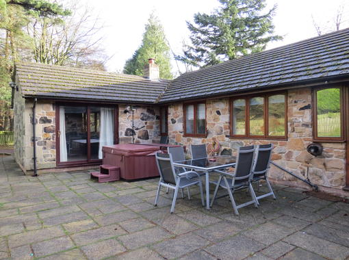 Patio area outside woodlands cottage showing hot tub and outside dining furniture