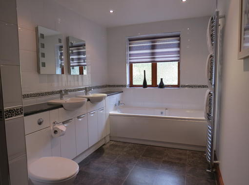 Spacious bathroom with his n hers sinks and full length bath
