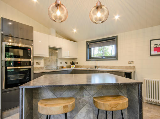 Modern kitchen area, with island and breafast bar with stools