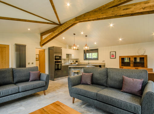 Spacious living area with comfortable grey sofas and light flooding in from the two sets of double doors